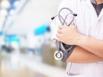 Doctor with a stethoscope in the hands and hospital background