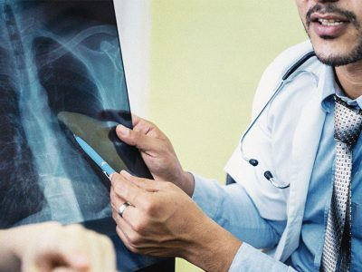 An Indian doctor is giving an explanation of his patients' lung x-rays.